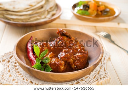 Indian curry chicken. Popular Indian dish on dining table. - stock photo