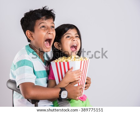 indian cute girl and boy eating popcorn, asian kids and popcorn, Little girl and little boy enjoy eating popcorn and. Leisure time for children, kids eating popcorn, isolated on white