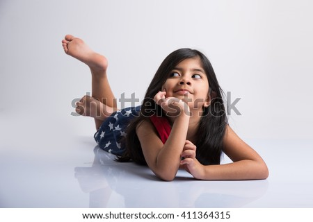 indian cute girl lying on the floor resting her head in her hands, asian Little girl laughing, lying on her stomach, isolated over white background - stock photo