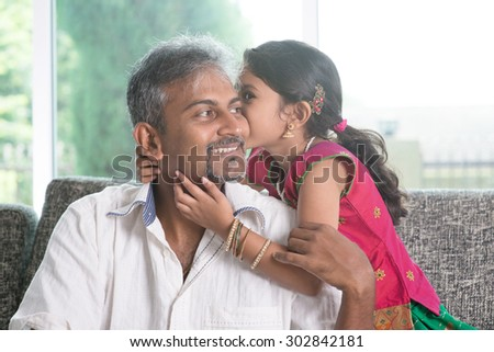 Indian daughter kissing father at home. Asian family indoors living lifestyle. - stock photo