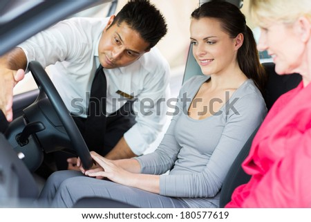 indian dealer explaining car features to potential customer - stock photo