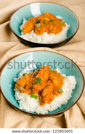 Indian dish - Chicken tikka masala served with rice and garnished with chopped cilantro - stock photo