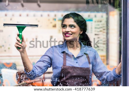 Indian employee cleaning windows with squeegee - stock photo