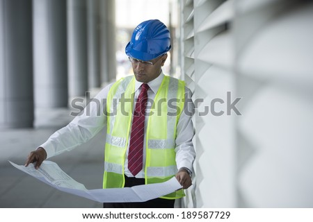 Indian engineer at work checking plans on industrial site. - stock photo