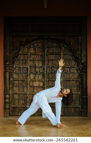 Indian ethnicity young man wit a strong body showing triangle yoga pose (Utthita Trikonasana) in front of old oriental style door. - stock photo