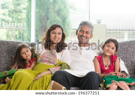 Indian family at home. Asian parents and children living lifestyle, sitting on couch indoor smiling happily. - stock photo