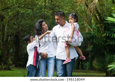 Indian family at outdoor. Parents and children walking on garden path. Exploring nature, leisure lifestyle. - stock photo