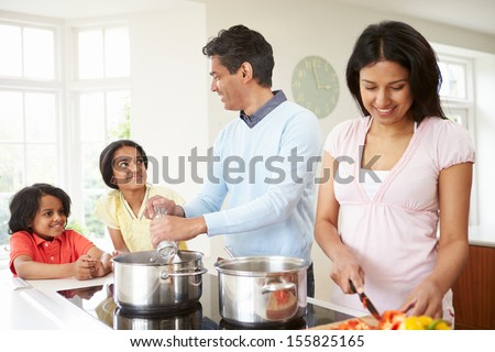 Indian Family Cooking Meal At Home - stock photo