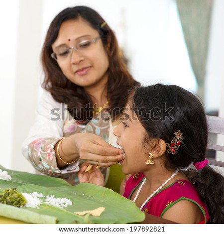 Indian family dining at home. Candid photo of Asian mother feeding rice to child with hand. India culture.