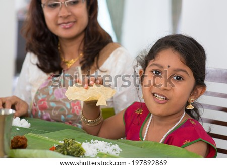 Indian family dining at home. Little girl eating snack papadum. India culture.