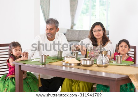 Indian family dining at home. Photo of Asian people eating rice with hands. India culture. - stock photo