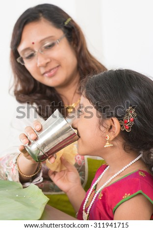 Indian family dining at home. Photo of child drinking water on dining table. Traditional home cook meal. - stock photo