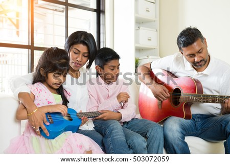 indian family enjoying quality time playing guitar at house