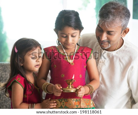 Indian family in traditional sari celebrate diwali or deepavali at home. Little girl hands holding oil lamp during festival of light. - stock photo