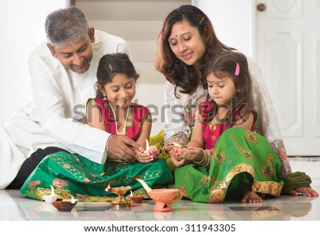 Indian family in traditional sari lighting oil lamp and celebrating Diwali, fesitval of lights at home. Little girl hands holding oil lamp indoors. - stock photo