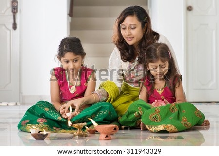 Indian family in traditional sari lighting oil lamp and celebrating Diwali, fesitval of lights at home.