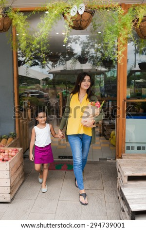 Indian family leaving supermarket after grocery shopping