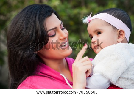 Indian family, mother holding her little daughter in arms - stock photo