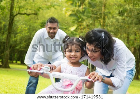 Indian family outdoor activity. Asian parent teaching child to ride a bike at the park in the morning. - stock photo