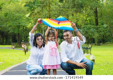 Indian family outdoor fun activity. Father and mother flying a colorful kite with daughter. - stock photo