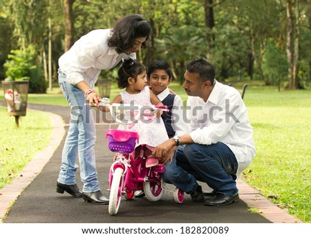 indian family teaching their kids cycling in the outdoor park - stock photo