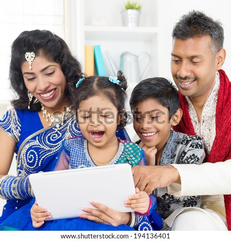 Indian family using digital computer tablet at home. Asian family living lifestyle. - stock photo