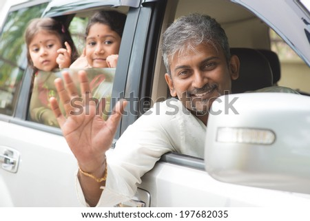 Indian family waving hands and saying goodbye, sitting in car ready to trip. Asian family lifestyle. - stock photo