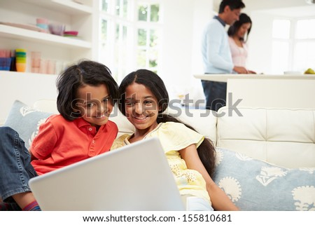 Indian Family With Laptop At Home - stock photo