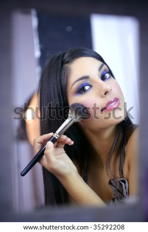 Indian fashion model makeup with brush on the mirror - stock photo