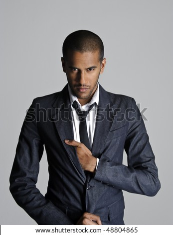 Indian fashion model stands in studio with his sharp suit - stock photo