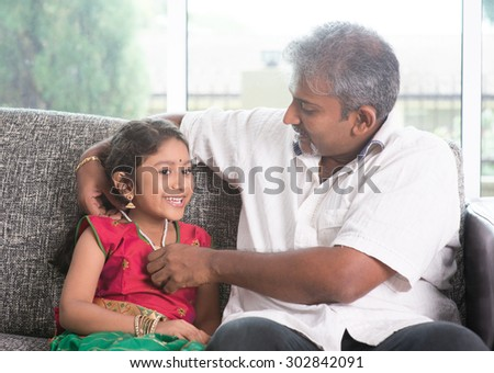 Indian father dressing daughter at home, preparing for diwali. Asian family indoors living lifestyle. - stock photo