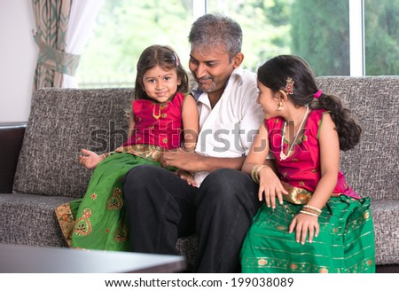 indian father with his daughter on living room - stock photo