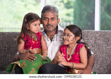 indian father with his daughter smiling and lookin at camera on living room - stock photo