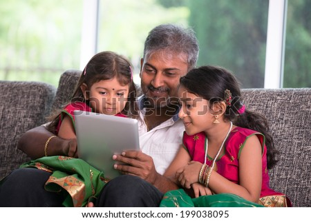 indian father with his daughter using a tablet computer on living room - stock photo