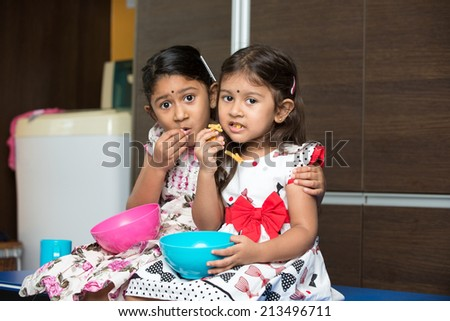 indian female sibling sister eating indoor - stock photo