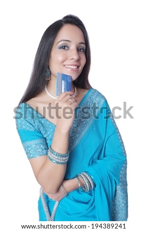 Indian female smiling with a credit/ debit card. - stock photo