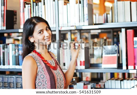 Indian female student at the library against book shelves
