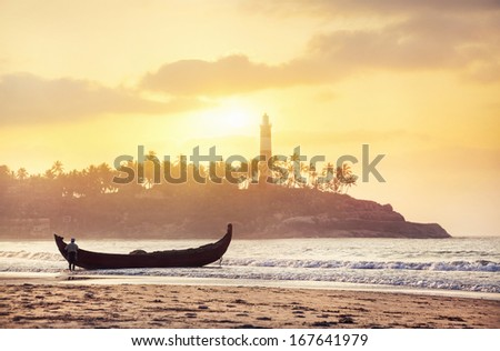 Indian fisherman in silhouette with fishing boat on the beach in the morning at lighthouse background in Kovalam, Kerala, India   - stock photo