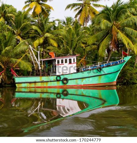 Indian fishing-boat with beautiful reflection in the water at famous backwaters of Kerala. Kochi, Kerala, India. - stock photo