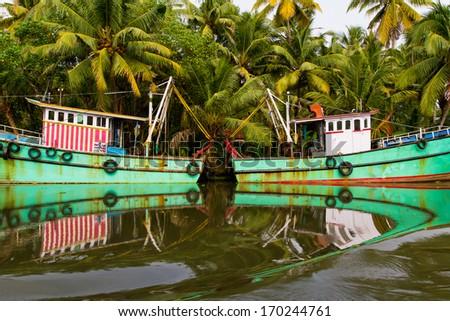 Indian fishing-boats with beautiful reflections in the water at famous backwaters of Kerala. Kochi, Kerala, India. - stock photo