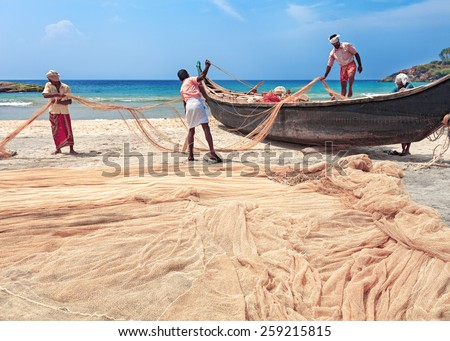 Indian fishing nets and traditional wooden boat - stock photo