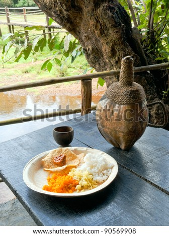Indian food. Rice with curry and traditional goan cashew fenny drink. Goa. India - stock photo