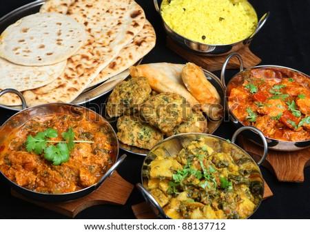 Indian food with curries, rice, naan bread, samosas and pakora. - stock photo