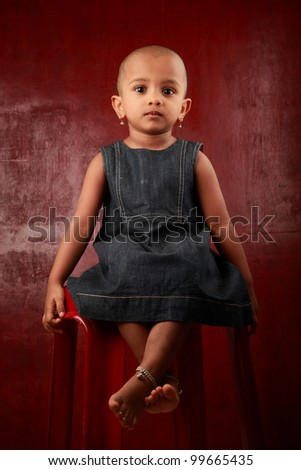 Indian girl child sits on a chair in a red background - stock photo