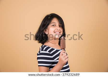 indian girl eating ice cream or ice candy, asian girl and ice cream or ice candy, isolated on brown background, ten year old indian girl enjoying ice cream - stock photo