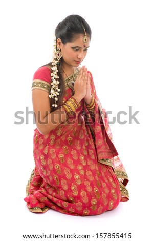 Indian girl in a greeting pose, traditional sari costume, full length kneeling on floor isolated on white background