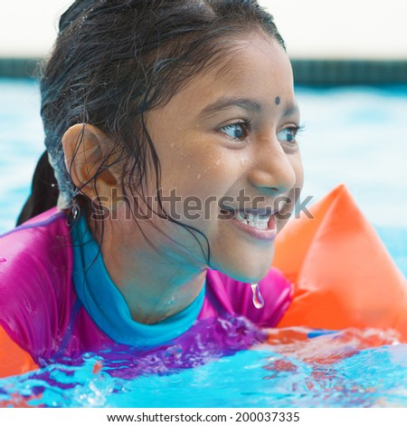 Indian girl learning swimming in pool. Asian child in swimmer class with float bands. - stock photo