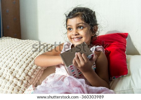 Indian girl open up with her present - stock photo