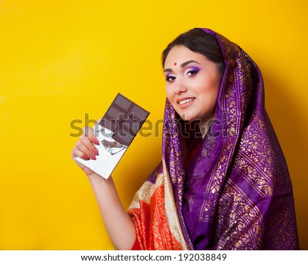 Indian girl with chocolate on yellow background. - stock photo