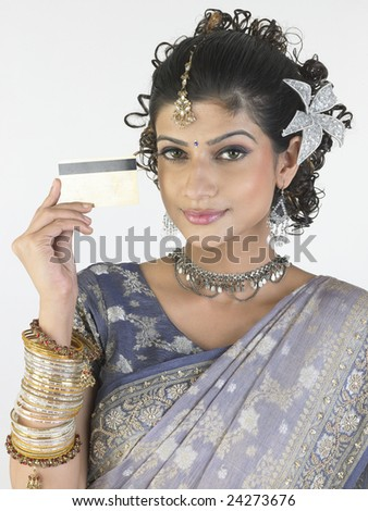 Indian girl with credit card thinking what to buy - stock photo